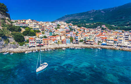 Parga village with boat sailing in the old harbour