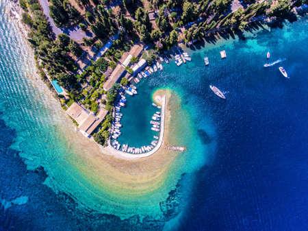 Kouloura old fishing village and beach. Corfu (Kerkyra) Island, Greece, Europe. Fishing boats and clear blue waters.