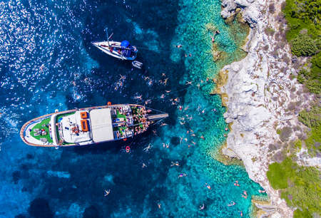 People swimming in the clear blue waters of Antipaxos Island, near Corfu - Kerkyra, Greece. Daily boat trips to the small island from Gaios town, Paxos.