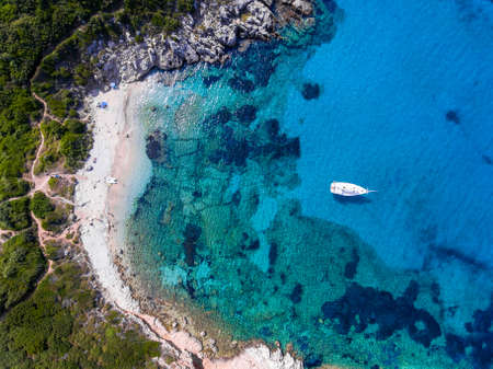 turqoise: Yacht sailing in the clear blue waters of Porto Timoni, Corfu, Greece, near a beautifull sandy beach. Aerial view.