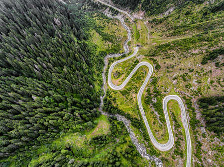 Winding road in the mountains. Forest, tunel and river visible, cars passing by. Transfagarasan road in Trasnylvania, Romania, Europe. Reklamní fotografie - 84049009