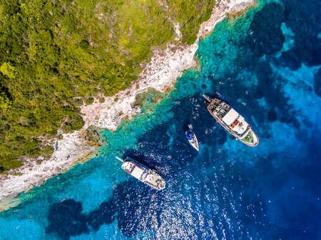 Mensen die in de duidelijke blauwe wateren van Antipaxos-Eiland zwemmen, dichtbij Korfu - Kerkyra, Griekenland. Luchtmening van een bootreis aan het kleine eiland van Gaios-stad, Paxos. Stockfoto