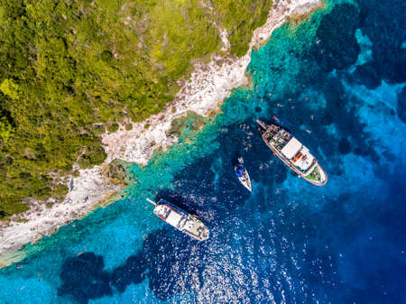 People swimming in the clear blue waters of Antipaxos Island, near Corfu - Kerkyra, Greece. Aerial view from a boat trip to the small island from Gaios town, Paxos.