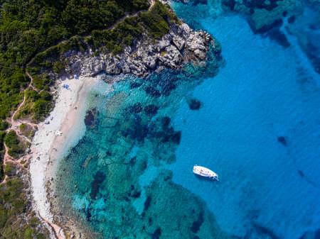Yacht sailing in the clear blue waters of Porto Timoni, Corfu, Greece, near a beautifull sandy beach.