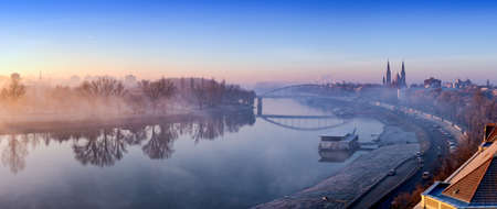 Szeged panorama with Tisza river and Votive Church visible in the back. Panoramic image at dusk with fog. HDR image. Stock Photo