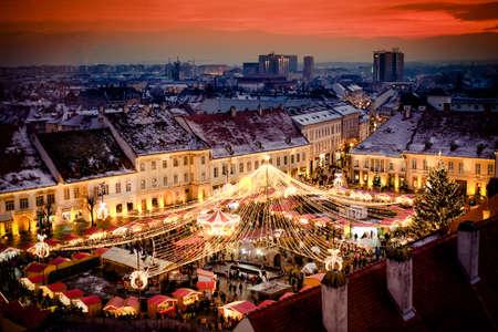 Mercado de Navidad en la plaza principal de Sibiu, Transilvania Rumania. Bonita puesta de sol en el corazón de Transilvania. La ciudad también conocida como Hermannstadt Editorial