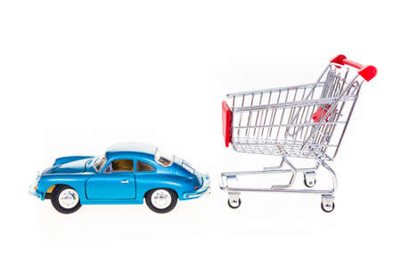 Car pulling shopping cart conceptual image isolated on white background