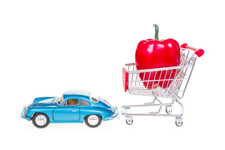 pushcart: Shopping cart with red bell pepper pulled by retro vintage car isolated on white background