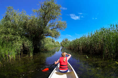 water ecosystem: Exploring Danube Delta in Canoe Boat Stock Photo