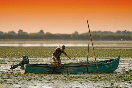Danube Delta, August 2017: Fisherman catching fish at sunrise in Delta Dunarii, Romania Stock Photo - 89043106