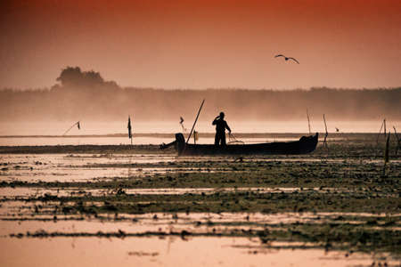 Fisherman in Danube Delta in the morning catching fish