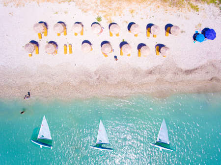 Summer beach in Lefkada Greece with sun umbrellas and sunbeds and yachts in the water