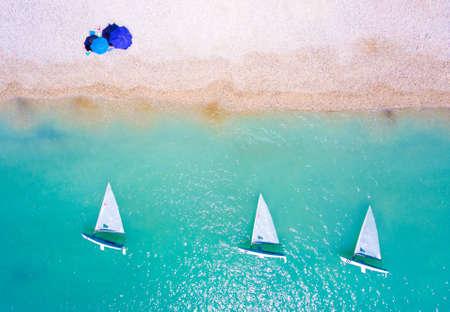 ヨットのボートと、レフカダ島の澄んだ青い海を持つビーチでの観光客