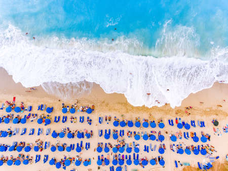 Birds-eye view of a beach with big waves, sunbeds and umbrellas in Lefkada, Greece