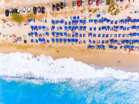 Sunbeds and umbrellas birds eye view on sand beach in Greece