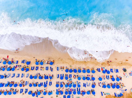 Birds eye view of a beach with big waves, sunbeds and umbrellas in Lefkada, Greece