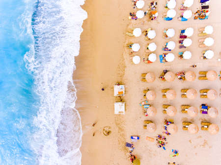 Sun charis and umbrellas birds eye view on sand beach in Greece