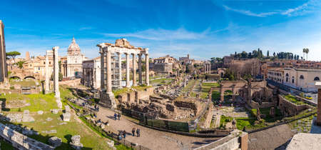 The ruins of the Roman Forum in Rome, Italy with the Colosseum visible in the back Редакционное