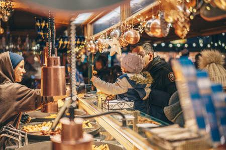 Salzburg, Austria - December 2018: Children receiveing treats the Salzburg Christmas Market at a street food stand