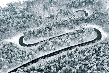 Curved winding road in the forest in winter time