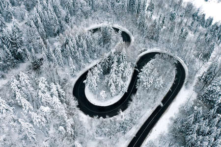 Winter highway trough a forest aerial view
