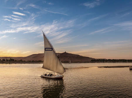 Tourist taking a ride in a Felucca boat in Luxor Egypt on the NIle River