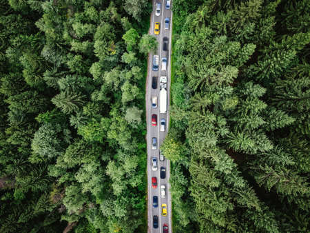Traffic jam on a road in the middle of a forest. Top down view of cars stuck in traffic. Aerial view shot with a drone (composite photo)
