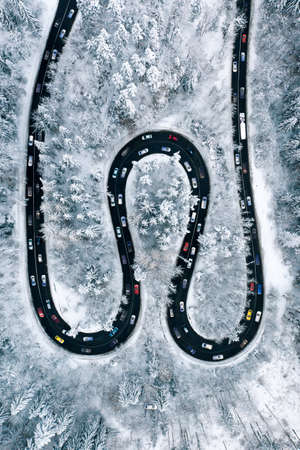 Winter traffic Jam on a highway trough the mountains. Aerial view of a rush hour traffic after a heavy snowfall. Winter weather and winter traffic conditions