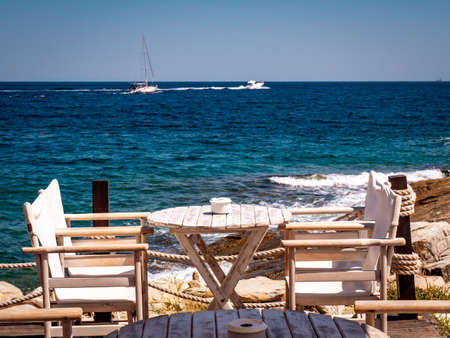 Greek tavern near the sea with wood chairs and table painted in white