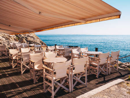 Traditional Greek Tavern near the sea with white wood furniture Stock Photo