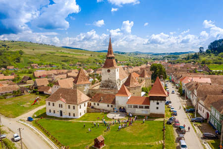 Aerial view of a saxon fortified Church in Transylvania, Romania, with blue sky and green grass