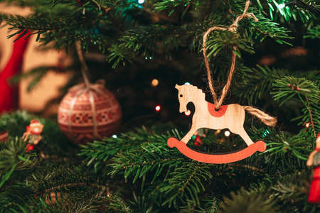 Horse decoration hanging in a Christmas tree. Equestrian postcard or background for Christmas greetings
