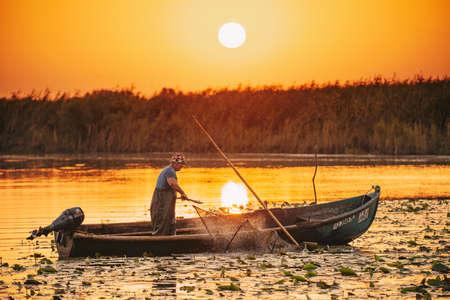 ROMANIA, DANUBE DELTA, AUGUST 2019: Sunrise in the Danube Delta. Fisherman checking the nets overnight catch