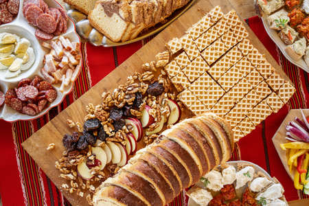 Fresh baked sweet bread and autumn nuts and apples surrounded by traditional food on a table at a local brunch in Romania