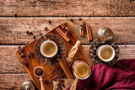 Top down view of coffee cups, beans and spices on a wood coffee table