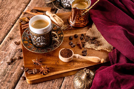 Detail of a cup of coffee and coffee beans on wood background Stock Photo