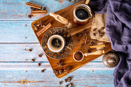 Coffee cups with coffee beans and pot. Vintage coffee arrangement on old wood background