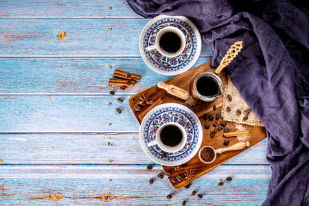 Ground coffee and coffee cups turkish style on blue background