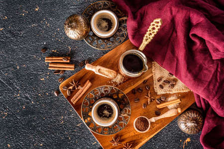 Cups of coffee and coffee beans on black background
