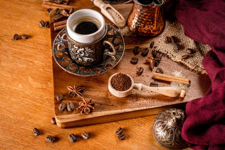 Detail of a coffee cup surrounded by coffee beans and spices on a natrual wood background Stock Photo