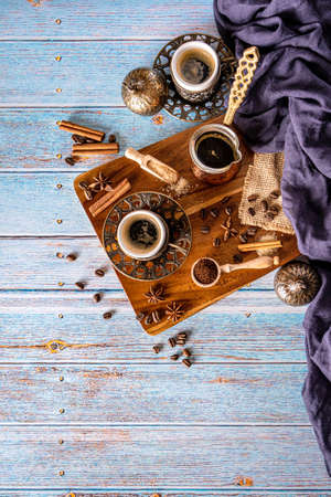 Arabic coffee cup with spices, coffee beans and ground coffee on a blue vintage background Zdjęcie Seryjne