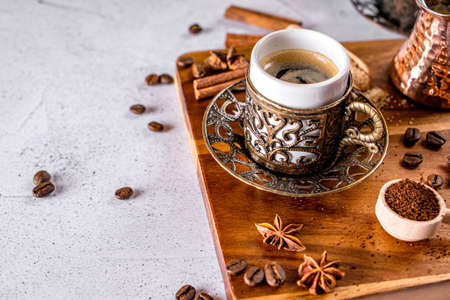 Oriental arabic style coffe cup with coffee beans and powder on a white table