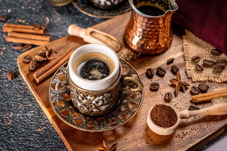 Cup of turkish coffee on black background with spices, coffee beans and sand coffee pot Stock Photo