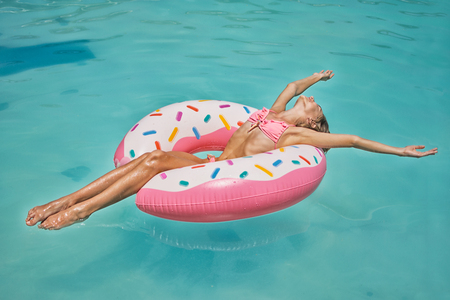 Enjoying suntan girl in bikini on the inflatable mattress in the swimming pool
