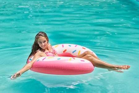 Smiling girl enjoys floating on inflatable donut in blue swimming pool