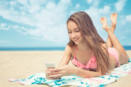 Pretty teenager girl using a smart phone lying on the beach with the sea and horizon in the background Stockfoto