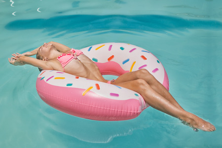 Girl in bikini on the inflatable donut mattress in the swimming pool enjoying sunbath