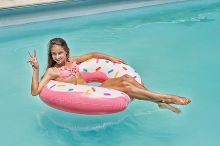 Teenage girl have fun on inflatable donut in blue swimming pool
