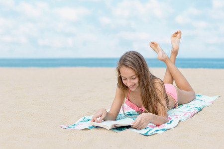 Pretty teenager girl reading book on the beach with the sea and horizon in the background Foto de archivo