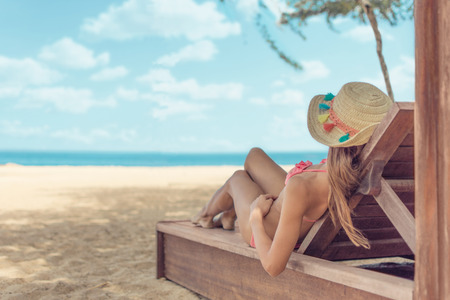Young woman whit sun hat relaxing on sun bad enjoys sunbath at the beach with the sea and horizon in the background on hot summer day travel and tourism concept